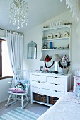 Romantic ornaments on chest of drawers and wall-mounted shelves and doll on rocking chair in white, child's bedroom