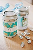 Decorated and labelled metal cans as gifts and silver decorative pebbles