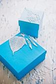 Fein ziselierte Blätter als Schmuck auf blauen Geschenkeschachteln