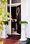 Eingansbereich mit Amphoren auf Säulen und Pudel in der geöffneten, mit einem Kranz geschmückten Haustür