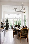 Armchairs with writing in gold on backs at festively set dining table; decorated Christmas tree in background