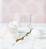 Empty glass with Easter decorations (egg shells, pussy willow, feathers)