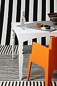White table and orange chair surrounded by various patterns of black and white stripes