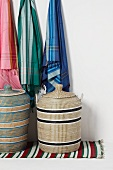 Scarves hanging above washing baskets on colourful woven rug