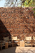 Gabion wall behind wire mesh; in front a circle of comfy armchairs with a side table