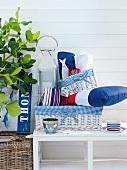 Korb mit Laterne und Kissen in nautischem Stil auf Sitzbank vor weisser Hausfassade