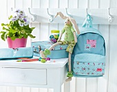 Child's bag set on white table and hanging on coat rack on white wooden wall
