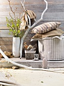 Various cushions and pouffe in shades of brown next to vase of flowers and branch against simple wooden wall