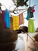 Beach towels hanging on construction of poles amongst boulders on beach