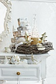 Stacked presents in willow wreath on shabby-chic table and Christmas baubles in open drawer