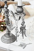 Key-shaped ornaments hanging from metal candlestick on table