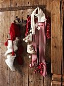 Baby clothes with festive motifs hanging from pegs on rustic wooden wall