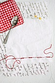 White napkin with red embroidery and jam spoon