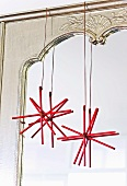 Home-made Christmas stars made from sticks hanging on a mirror