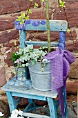 Blue chair with plants in a galvanized bucket