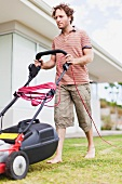 Man mowing lawn in front of house
