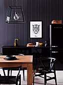 Classic chairs on a wooden table in front of a black kitchen counter on a black wooden wall