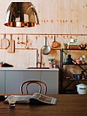 Thonet chair on a wooden table, in the background a kitchenette under hanging cookware on a wooden wall