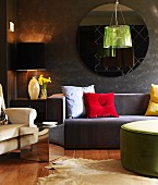 Bright scatter cushions and lustrous green pendant lamp providing accents of colour combined with sofas in muted colours and anthracite walls