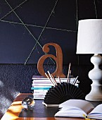 Wooden letter on stack of magazines, fan-shaped pen holder and country-house-style lamp on desk against wall decorated in black