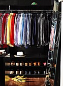 Shirts arranged by colour and shoes in black-painted, walk-in wardrobe