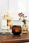 Blocks of soap in glass vessel, tealight in dark lantern and flowering branch in vase