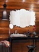 Elegant black washstand with artwork on fine wooden paneling, various flacons and silver-colored mirrors