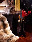 Fur blankets, black side table, lit gold candles and red orchid flowers in glamorous bedroom