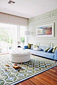 White ottoman on rug with graphic pattern and long blue couch against wall with classic, pastel green wood panelling