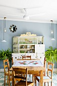 Kitchen-dining room with simple, plain wood dining set; antique kitchen dresser, adjustable pendant lamps and ferns against pale blue wall