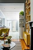 Wohnzimmer in Gelb-Grüntönen und im Hintergrund Küche in Blautönen