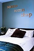 The word 'sleep' written in three languages decorating wall painted slate blue above double bed