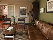 Living room in shades of brown with leather couch, coffee table and chairs