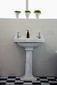 Pedestal wash basin against white-tiled wall