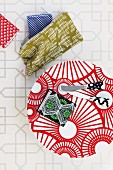 Knives and pencil case on red and white patterned plate