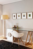 Classic chair at glass table top resting on trestle and drawer cabinet; standard lamp with ornate metal base and small, colourful artworks on wall