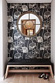 Round, latticed window on floral wallpaper and bench with black leather seat cushion in niche