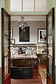 Blick durch geöffnete Glasflügeltür auf Vintage Schlafzimmer mit alten Koffern vor verziertem Eisenbett