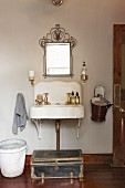 Wrought iron mirror above old stone sink with perfume bottles: enamel bucket of fresh towels hung on wall and antique trunk