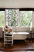Bathtub with brass claw feet below window with wrought iron grille; trolley of toiletries