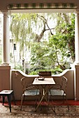 Old metal chairs and metal table in loggia with antique stone columns; view into lush courtyard