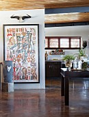 Free-standing sculpture and artwork on wall in open-plan interior with rustic wood-beamed ceiling