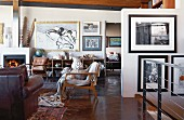 Various armchairs in lounge area and collection of modern artworks on walls in open-plan interior