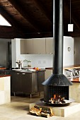 Wood-burning stove in open-plan interior in front of kitchen area with island counter and grey fitted units