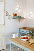Kitchen table with pale blue frame in front of vintage kitchen counter in corner below swallow-shaped sconce lamps
