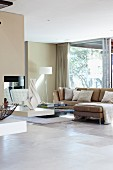 Bright interior in natural shades with sofa combination next to glass wall