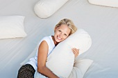 Young woman hugging pillow on bed