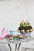 Blumengesteck mit rosaroten Rosen, Moos und Kerze in altem Emailletopf, daneben Rosenbouquets in Porzellanförmchen