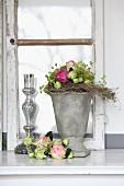 Rosendekoration mit Vasen aus Stein und Glas vor altem Fensterflügel