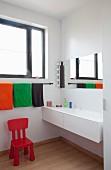 Roter Kinderstuhl unter aufgehängten Handtüchern und modernes Waschbecken in Badezimmer